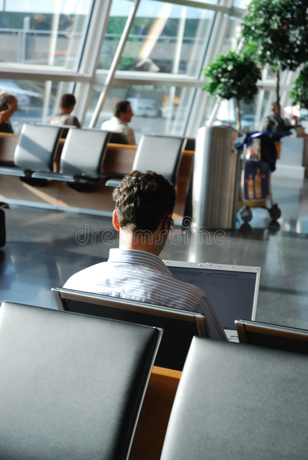 Viajante de negócio que espera em uma sala de estar do aeroporto foto de stock