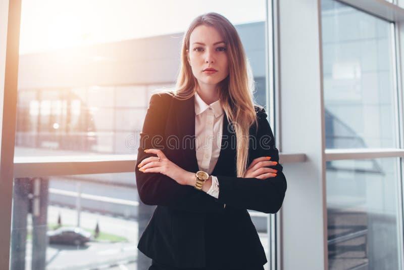 Viajante de negócios fêmea que está contra a janela com opinião do corredor da chegada do aeroporto foto de stock