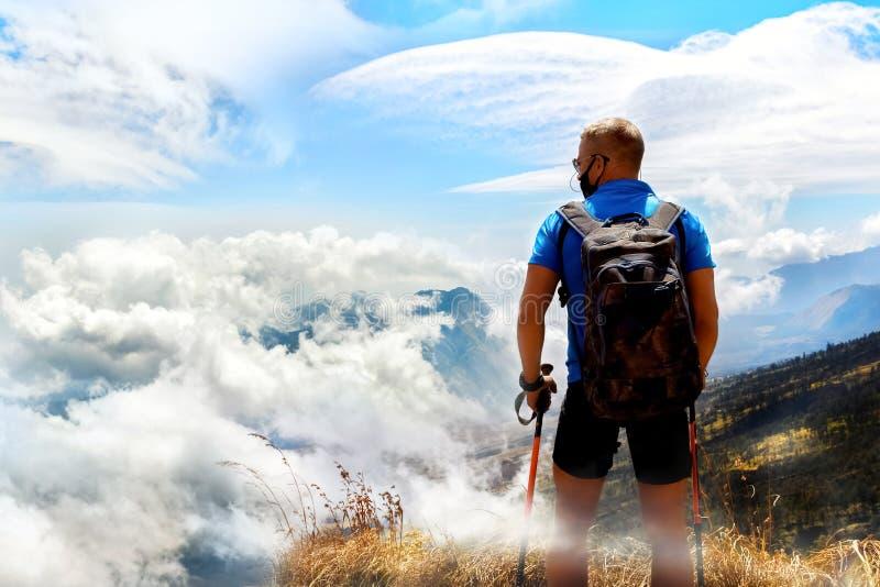 Viajante desportivo do indivíduo com trouxa em um fundo de um céu bonito com as nuvens nas montanhas Acima das nuvens indonésia fotos de stock