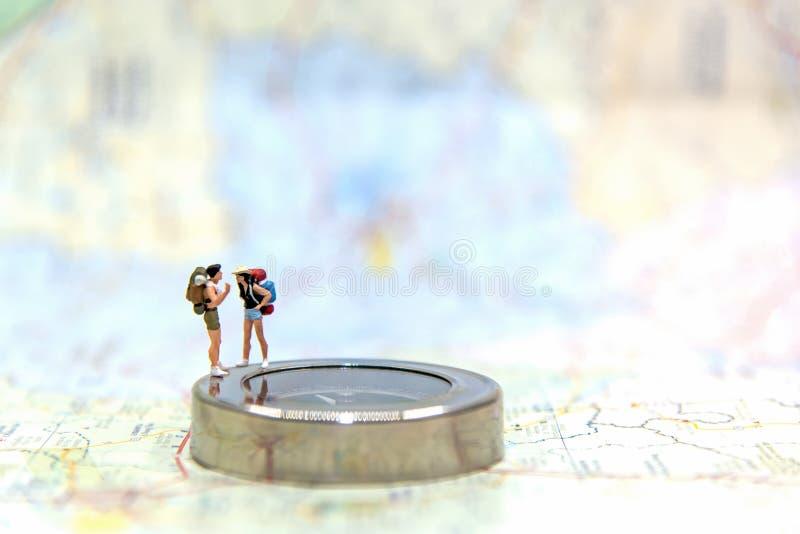 Viajante diminuto do grupo com a trouxa que está no mapa do wold para o curso em todo o mundo fotos de stock royalty free