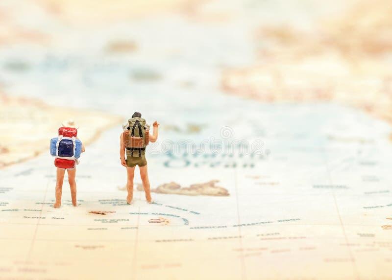 Viajante diminuto do grupo com a trouxa que está no mapa do wold para o curso em todo o mundo imagem de stock royalty free