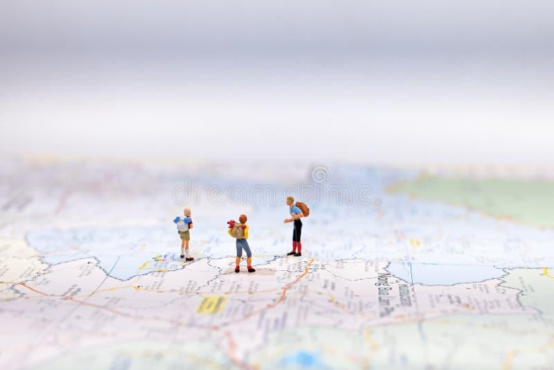 Viajante diminuto do grupo com a trouxa que está no mapa do wold para o curso em todo o mundo Conceito do curso, fotografia de stock