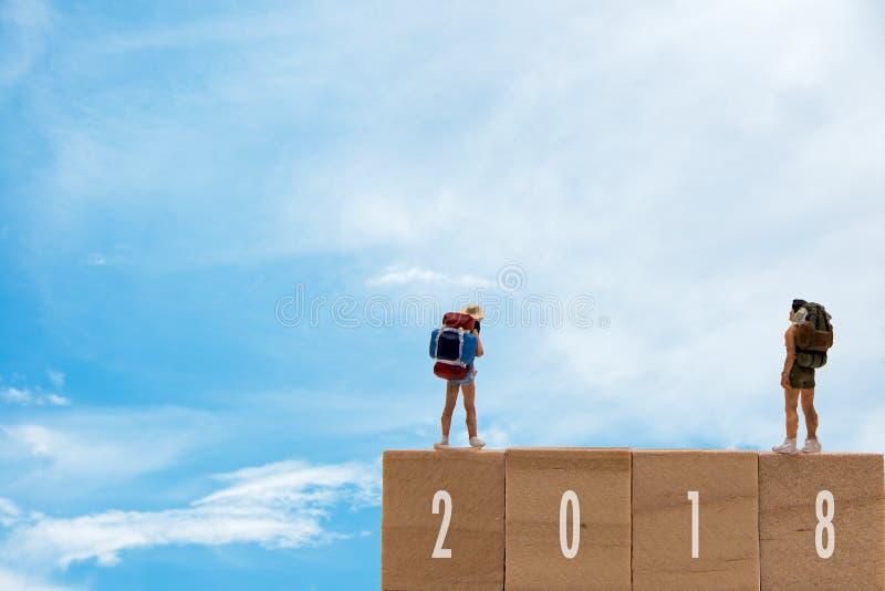 Viajante diminuto do grupo que está em 2018 de madeira com ano novo, fundo do céu azul foto de stock royalty free