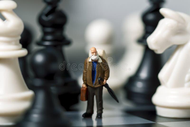 Viajante diminuto e xadrez da boneca Viajante idoso no tabuleiro de xadrez imagens de stock royalty free