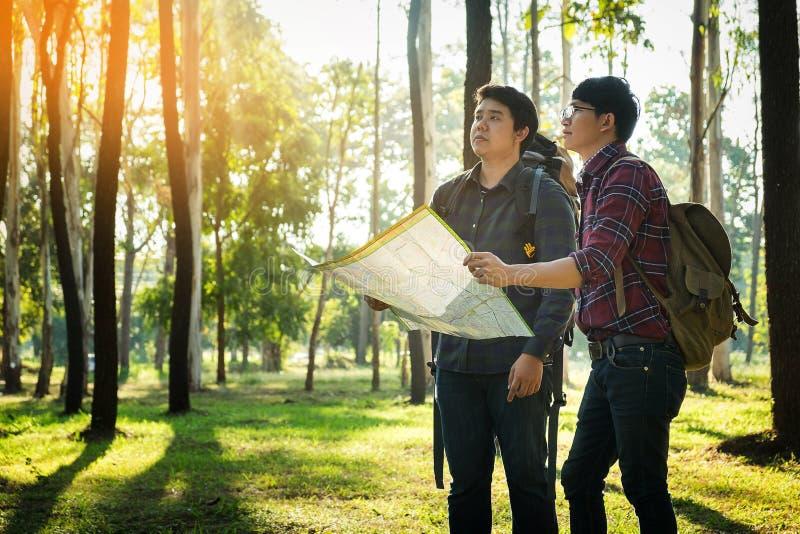 Viajante do homem dois novo com o relaxamento do mapa do punho da trouxa exterior fotografia de stock