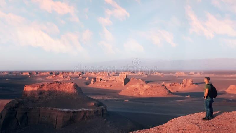 Viajante do homem no fundo de formações rochosas no deserto de Dasht e Lut contra o por do sol Queda de Sheykh Alikhan persia foto de stock royalty free