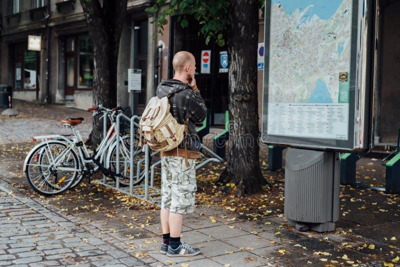 Viajante do homem novo que olha ao mapa da cidade na rua imagens de stock royalty free