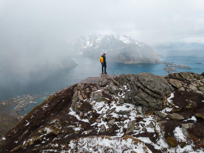 Viajante do homem que caminha no cume da montanha de Reinebringen na viagem da aventura do estilo de vida de Noruega fotos de stock