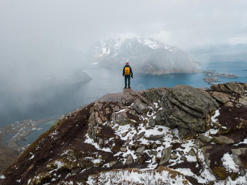 Viajante do homem que caminha no cume da montanha de Reinebringen na viagem da aventura do estilo de vida de Noruega imagem de stock royalty free