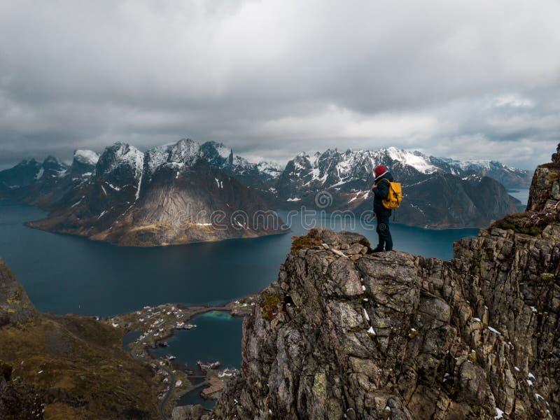Viajante do homem que caminha no cume da montanha de Reinebringen na viagem da aventura do estilo de vida de Noruega fotografia de stock royalty free