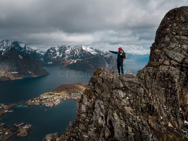 Viajante do homem que caminha no cume da montanha de Reinebringen na viagem da aventura do estilo de vida de Noruega foto de stock