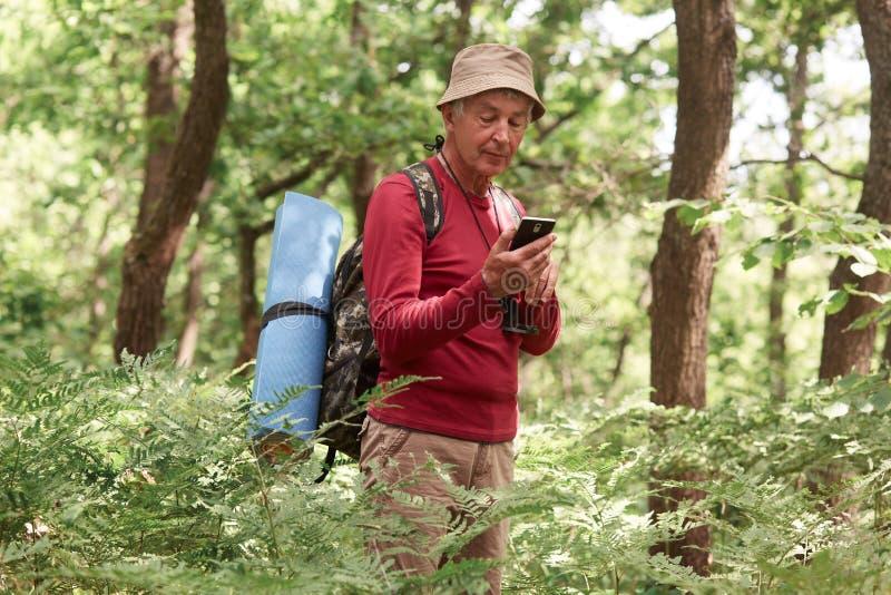 Viajante experiente que guarda seu smartphone em uma mão, usando o dispositivo para orientar, sendo apenas, tendo o compasso e o  foto de stock