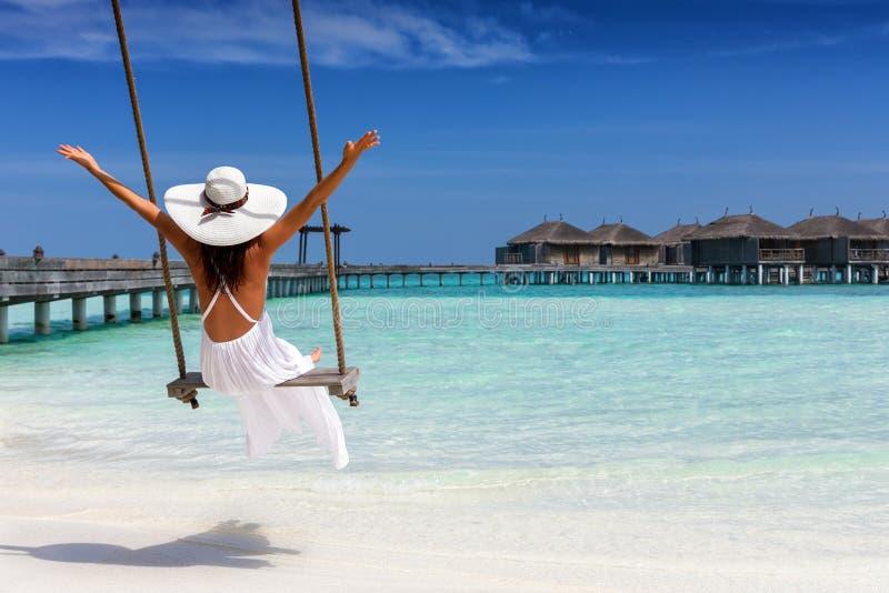 Viajante fêmea feliz em um balanço em uma praia tropical fotos de stock royalty free