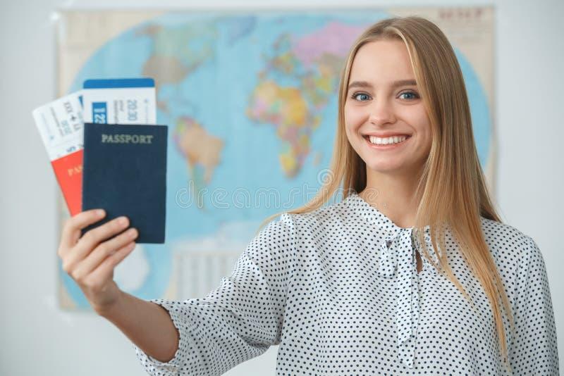 Viajante fêmea louro novo em uma agência da excursão que guarda passaportes imagens de stock