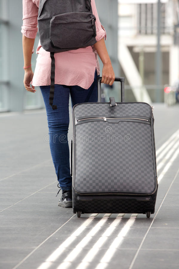 Viajante fêmea novo que anda afastado com mala de viagem imagem de stock