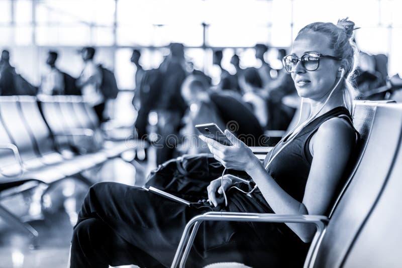 Viajante fêmea que usa seu telefone celular ao esperar para embarcar um plano em portas de partida no terminal de aeroporto asiát imagem de stock