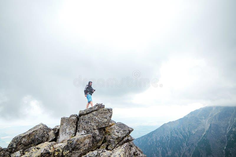Viajante feliz do homem com a câmera na borda de um penhasco nas montanhas imagem de stock