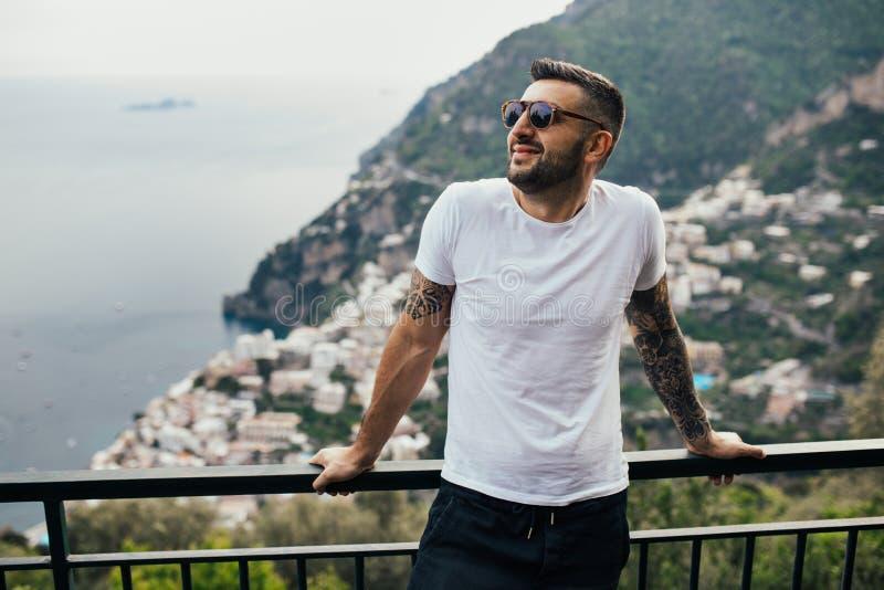 Viajante feliz do homem novo que sorri na opinião italiana da costa Homem que viaja ao tempo ensolarado coastEnoying sul europeu  foto de stock royalty free