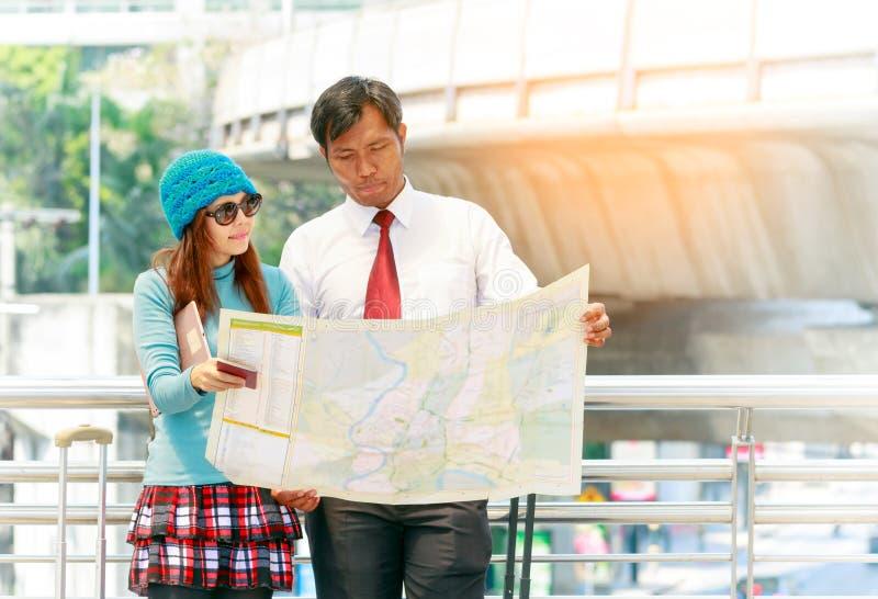 Viajante feliz dos pares com a bagagem que olha o guia do mapa na cidade fotos de stock