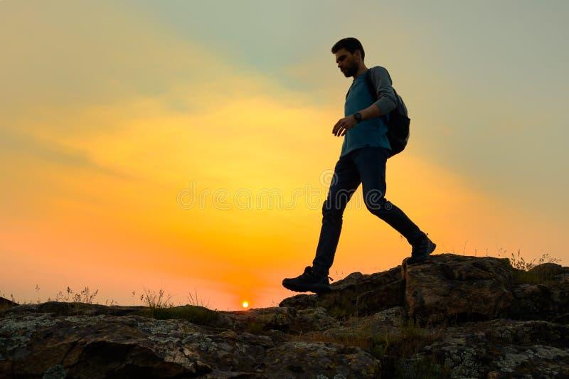 Viajante feliz novo do homem que caminha com a trouxa em Rocky Trail no por do sol morno do ver?o Conceito do curso e da aventura imagem de stock