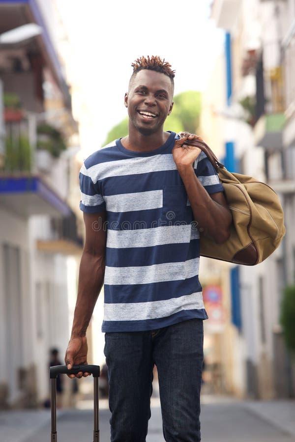 Viajante masculino africano novo que anda na rua com sacos fotos de stock royalty free
