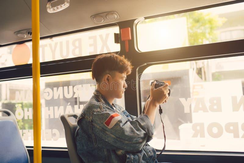 Viajante masculino asiático que toma a foto da cidade da janela de foto de stock
