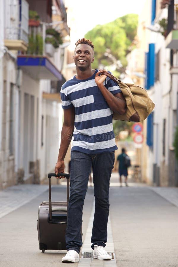 Viajante masculino novo do comprimento completo que anda na rua com mala de viagem fotos de stock