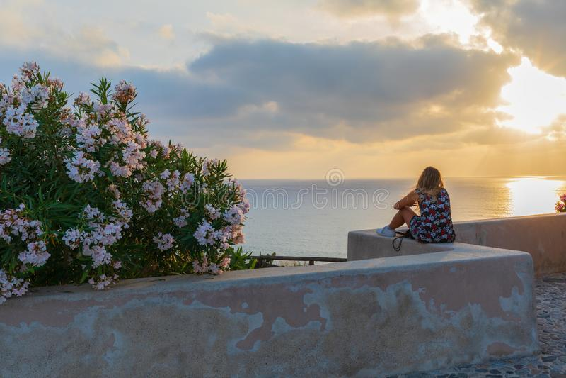 Viajante novo da mulher do moderno que olha o por do sol e o seascape bonito em férias de verão com um ponto da vigia fotografia de stock