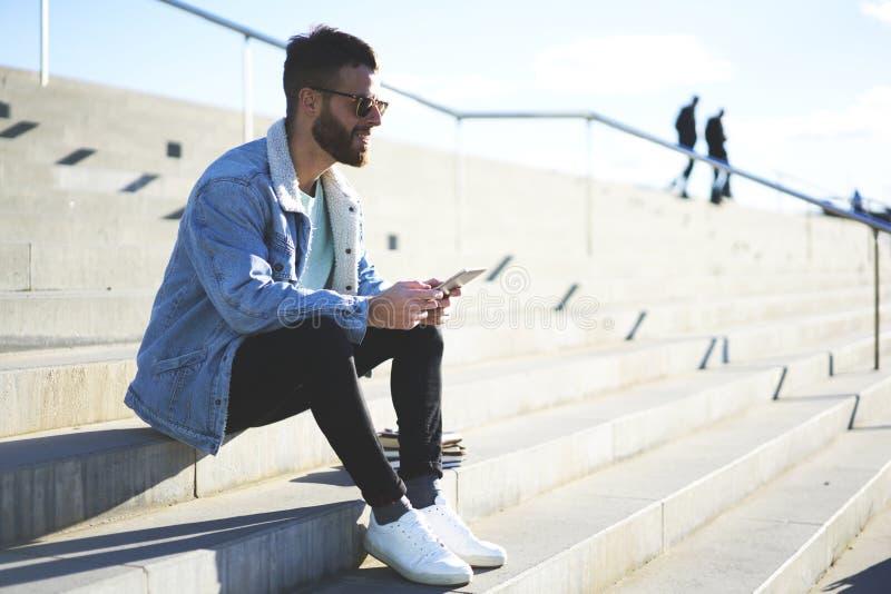 Viajante novo do blogger do moderno em um revestimento da sarja de Nimes que aprecia a luz do sol fora foto de stock royalty free