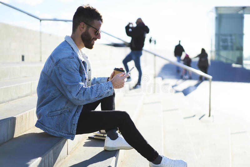 Viajante novo do blogger do moderno em um revestimento da sarja de Nimes usando o smartphone e Internet 4G com amigos fotos de stock royalty free