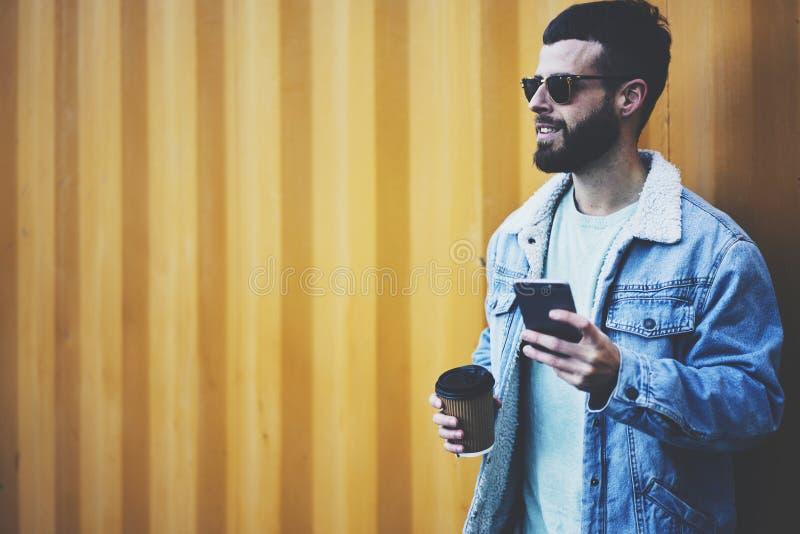 Viajante novo do blogger do moderno em um revestimento da sarja de Nimes usando o smartphone moderno e Internet rápido em vaguear fotos de stock