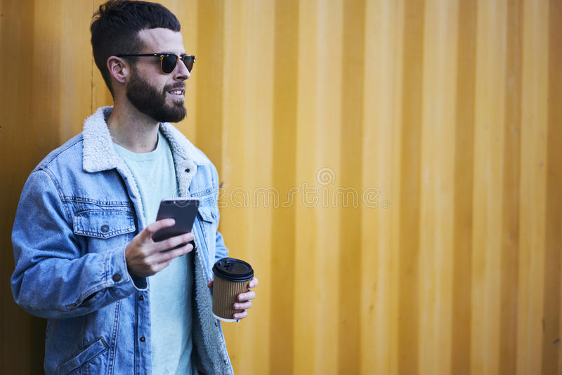 Viajante novo do blogger do moderno em um revestimento da sarja de Nimes usando o smartphone moderno e Internet rápido em vaguear imagem de stock royalty free