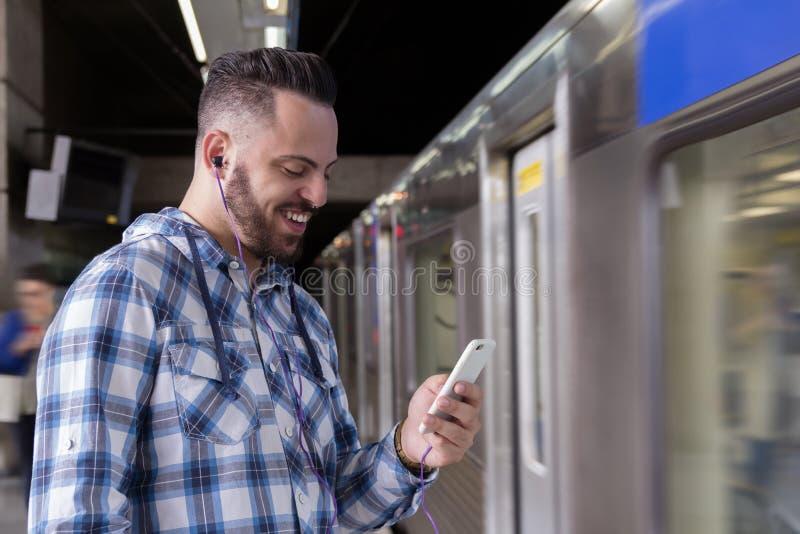 Viajante novo em uma plataforma do trem que escuta a música em um smartphone O conceito de comuta, viaja, conexão imagem de stock royalty free
