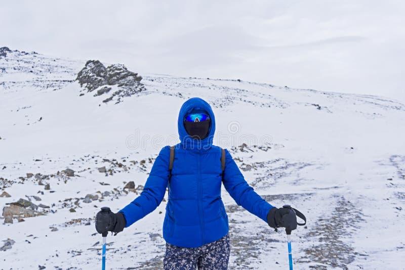 Viajante ou esquiador em uma máscara windproof e vidros da menina nas montanhas do inverno imagens de stock royalty free