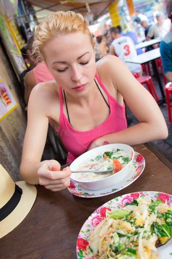Viajante que come a sopa tailandesa tradicional de Tom Yum imagem de stock