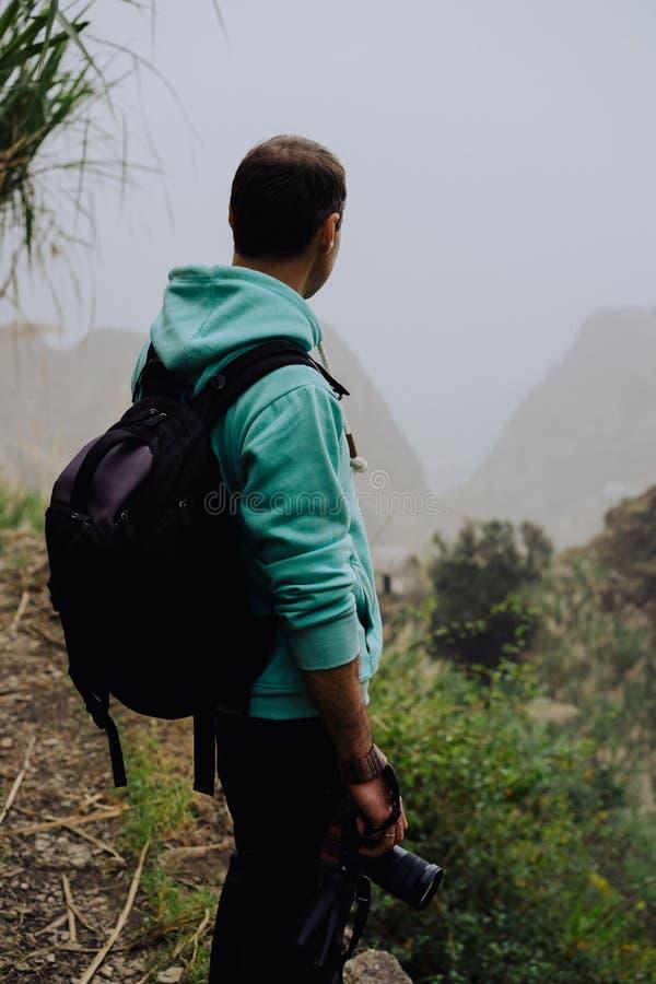 Viajante que guarda o suporte da câmera na frente da paisagem rural com montanhas e a ravina de Paul Valley Santo Antao foto de stock royalty free