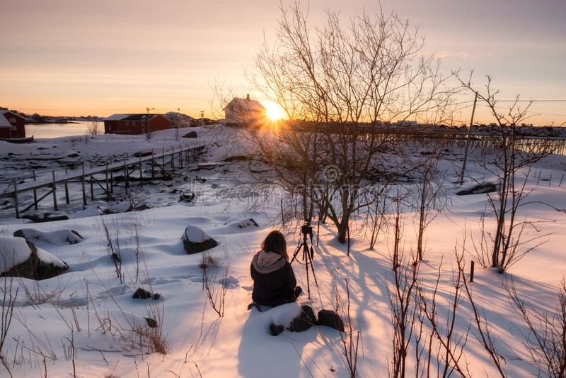 Viajante que senta-se em nevado com a câmera no tripé e o nascer do sol na casa branca fotos de stock royalty free