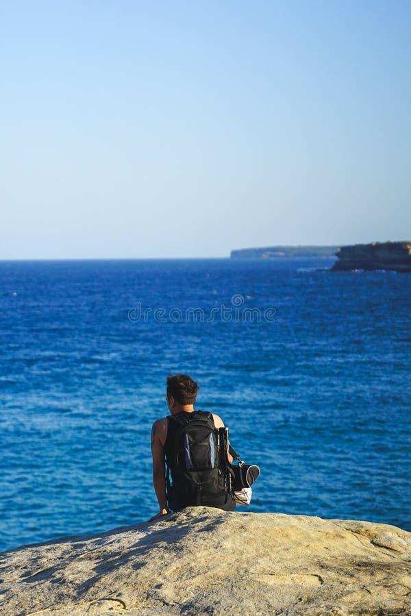 Viajante que senta-se na borda do penhasco da rocha, olhando ao azul fotos de stock