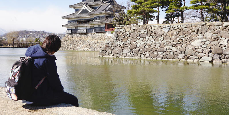 Viajante que senta-se no lago em torno da parte do castelo japonês imagem de stock royalty free