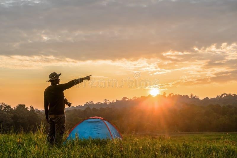 Viajante que tem o acampamento com a barraca no campo de grama na manhã imagem de stock