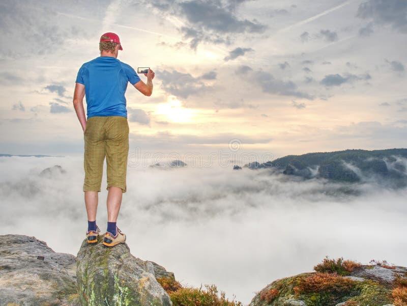 Viajante que toma fotos móveis das férias do por do sol bonito na natureza do outono imagens de stock royalty free