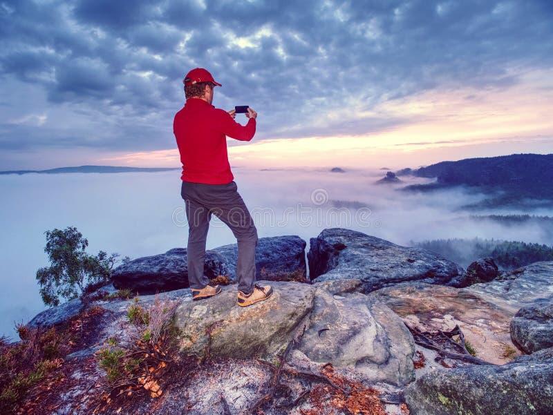Viajante que toma fotos móveis das férias do por do sol bonito na natureza do outono foto de stock
