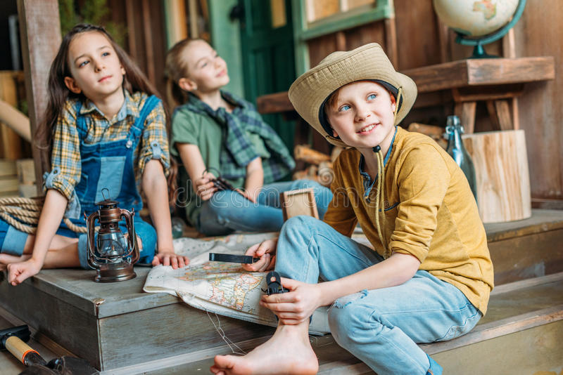 Viajantes das crianças que sentam-se junto com o mapa no patamar fotografia de stock