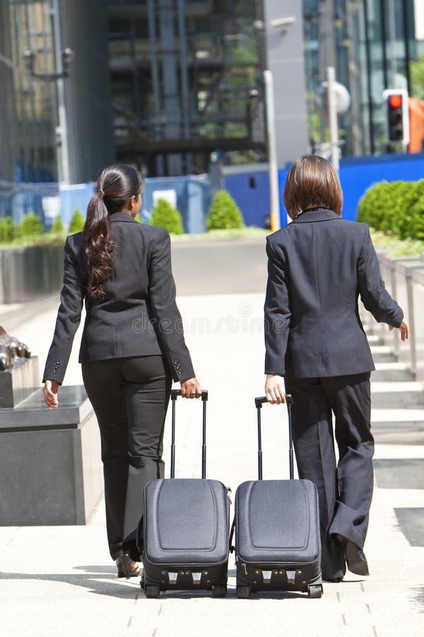 Viajantes de negócio das mulheres com malas de viagem do rolamento