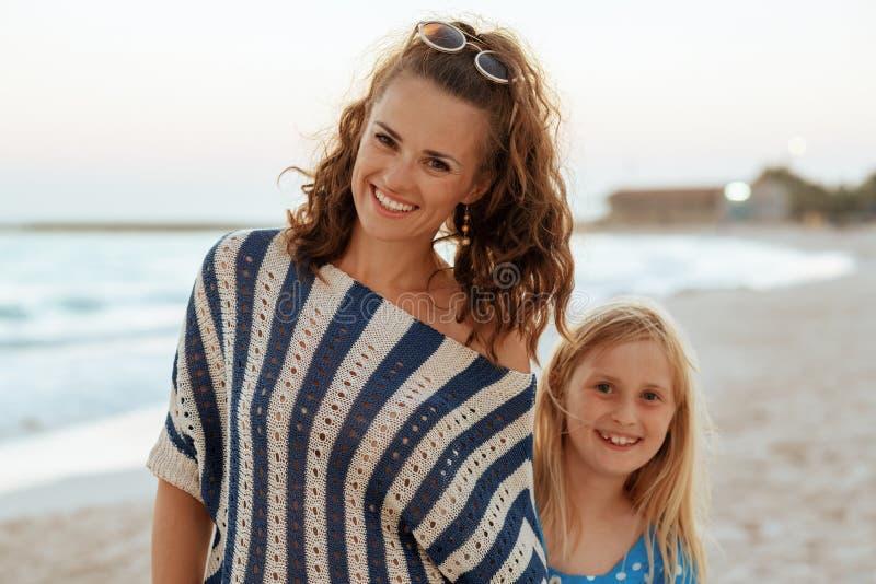 Viajantes de sorriso da mãe e da criança na praia na noite foto de stock