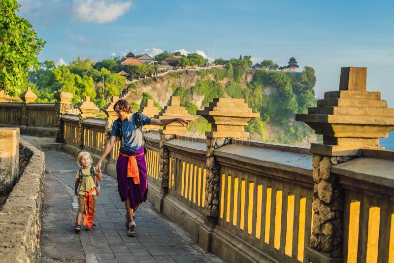 Viajantes do paizinho e do filho no templo de Pura Luhur Uluwatu, Bali, Indonésia Paisagem surpreendente - penhasco com céu azul  foto de stock