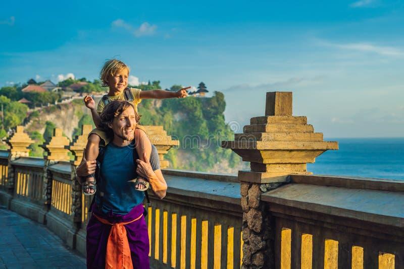 Viajantes do paizinho e do filho no templo de Pura Luhur Uluwatu, Bali, Indonésia Paisagem surpreendente - penhasco com céu azul  imagem de stock royalty free
