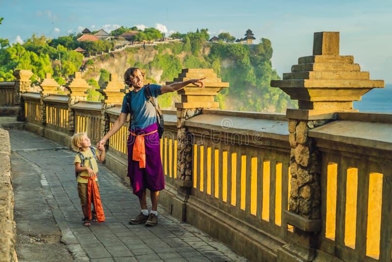 Viajantes do paizinho e do filho no templo de Pura Luhur Uluwatu, Bali, Indonésia Paisagem surpreendente - penhasco com céu azul  fotografia de stock
