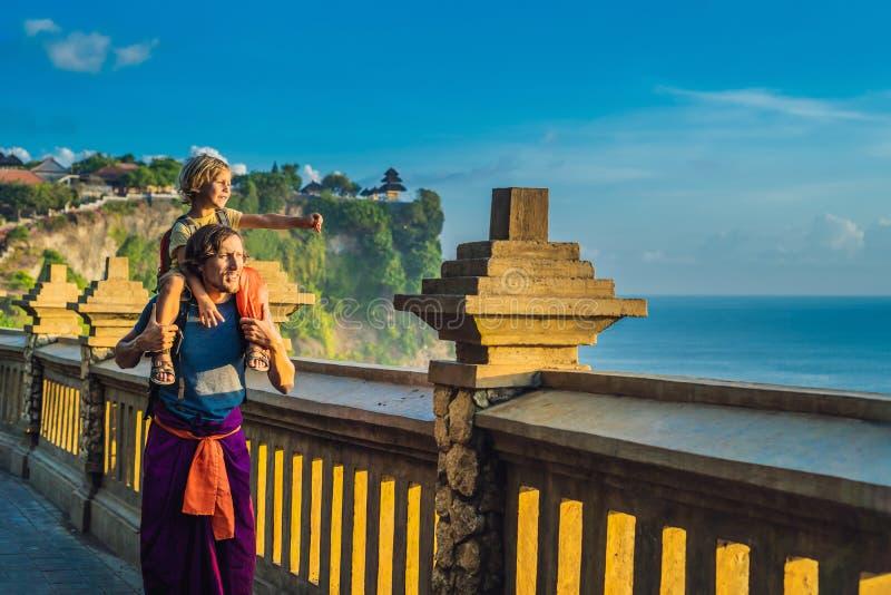 Viajantes do paizinho e do filho no templo de Pura Luhur Uluwatu, Bali, Indonésia Paisagem surpreendente - penhasco com céu azul  imagem de stock