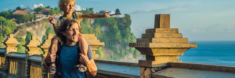 Viajantes do paizinho e do filho no templo de Pura Luhur Uluwatu, Bali, Indonésia Paisagem surpreendente - penhasco com céu azul  imagens de stock